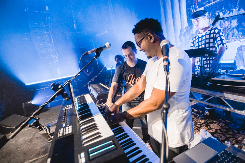 Kevin Randolph collaborating with another artist on stage while playing MONTAGE synthesizer.